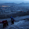 Three Afghan children, one carrying bricks, walk up a steep hillside overlooking Kabul, Afghanistan, Wednesday, Feb. 3, 2010. (AP Photo/Brennan Linsley)