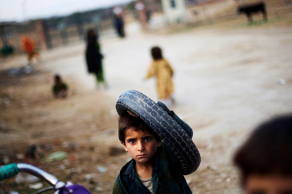 An Afghan refugee boy carrying a tire is seen at his camp, on the outskirts of Islamabad, Pakistan, Thursday, Feb. 4, 2010. (AP Photo/Muhammed Muheisen)