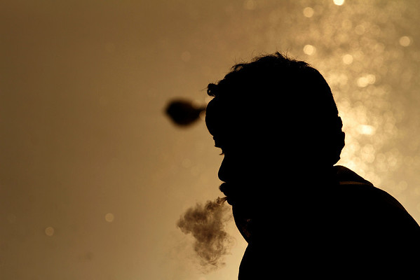 A man is seen silhouetted as he smokes on the banks of the River Yamuna in New Delhi, India, Friday, Feb. 5, 2010. (AP Photo/Rajesh Kumar Singh)