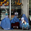 Afghan women wait sitting in front of a pharmacy in Kabul, Afghanistan on Sunday, Feb. 21, 2010. (AP Photo/Rahmat Gul)