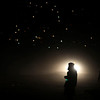 An Afghan man is silhouetted as he waits for transport in Kabul, Afghanistan, Thursday, Feb. 4, 2010, as lights in the background are from dwellings on hill side. (AP Photo/Altaf Qadri)