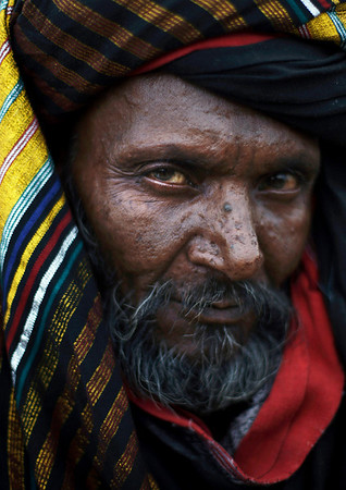 Pakistani Mohammed Shafi, 55, who makes his living by hunting snakes, looks on while seen in a slum on the outskirts of Islamabad, Pakistan, Saturday, Feb. 20, 2010. (AP Photo/Muhammed Muheisen)
