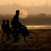 A man cycles his children to school early morning in New Delhi, India, Friday, Feb. 5, 2010. (AP Photo/Rajesh Kumar Singh)