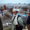 Three Afghan refugees look on while seen standing next to their camp on the outskirts of Islamabad, Pakistan, Monday, Feb. 22, 2010. (AP Photo/Muhammed Muheisen)