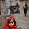 A young Afghan refugee girl looks on while walking in an alley during a rainy day in a poor neighborhood of Rawalpindi, Pakistan, Friday, Feb. 5, 2010. (AP Photo/Muhammed Muheisen)