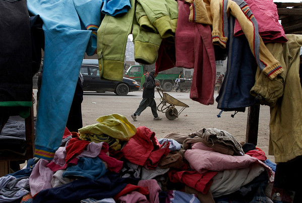 An Afghan youth is seen through second-hand clothes as he pushes his empty cart to be hired in Kabul, Afghanistan on Sunday, Feb. 21, 2010. (AP Photo/Musadeq Sadeq)