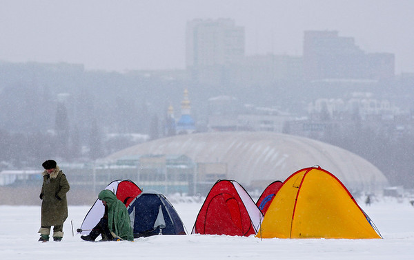 Ukrainian fishermen protect themselves from the cold wind as they sit on the frozen Dnepr River in Dnipropetrovsk, Ukraine, Friday, Feb. 5, 2010. (AP Photo/Sergei Grits)