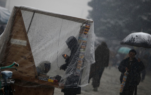 An Afghan man lights a cigarette at a roadside vendor covered with plastic as it snows in Kabul, Afghanistan, Friday, Feb. 5, 2010 (AP Photo/Altaf Qadri)