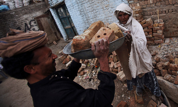 Pakistani Piary Bibi, 70, helps her son to carry bricks as they build a house in a Christian neighborhood, on the outskirts of Islamabad, Pakistan, Saturday, Feb. 20, 2010. (AP Photo/Muhammed Muheisen)