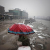 An Afghan roadside vendor waits for customers as he sits under an umbrella while it snows in Kabul, Afghanistan, Friday, Feb. 5, 2010. (AP Photo/Altaf Qadri)