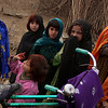 An Afghan street tailor shows a girl her dress, while other girls look on at their camp, on the outskirts of Islamabad, Pakistan, Thursday, Feb. 4, 2010. (AP Photo/Muhammed Muheisen)