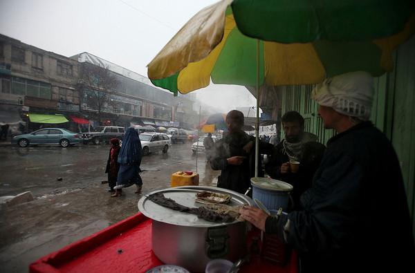 Afghans drink hot soup at a roadside vendor as it snows in Kabul, Afghanistan, Friday, Feb. 5, 2010 (AP Photo/Altaf Qadri)