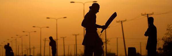Pakistanis play cricket in a field, during sunset on the outskirts of Islamabad, Pakistan, Thursday, Feb. 4, 2010. (AP Photo/Muhammed Muheisen)