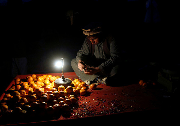 An Afghan street vendor counts his money before leaving for the evening at a market in Kabul, Afghanistan on Saturday, Feb. 20, 2010. (AP Photo/Rahmat Gul)