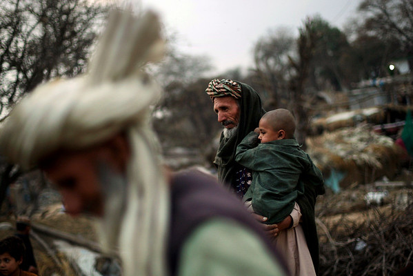 An elderly Afghan refugee, Noroas Khan, who works as a tractor driver, holds his grandson Ghafar while seen heading to a mosque next to their camp on the outskirts of Islamabad, Pakistan, Monday, Feb. 22, 2010. (AP Photo/Muhammed Muheisen)