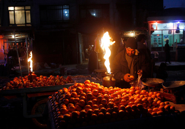 An Afghan man collects oranges during a night at a market in Kabul, Afghanistan on Saturday, Feb. 20, 2010. (AP Photo/Rahmat Gul)