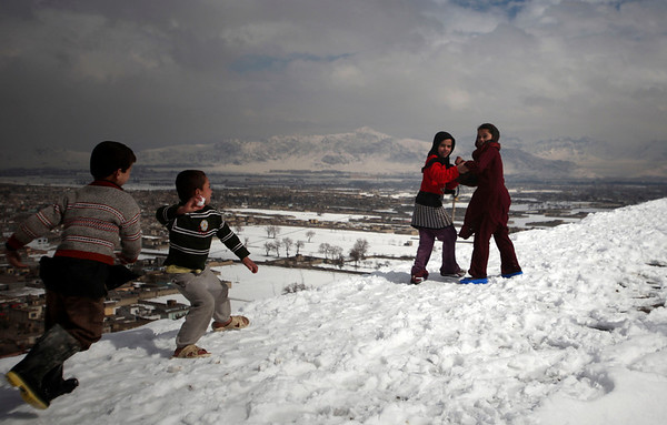 A young Afghan boy aims a snowball towards two girl on a hilltop in Kabul, Afghanistan, Monday, Feb. 8, 2010. (AP Photo/Altaf Qadri)