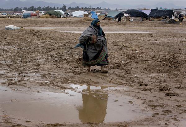 An Afghan nomad woman walks on mud after a rainfall in Kandahar, south of Kabul, Afghanistan, Monday, Feb. 8, 2010. (AP Photo/Allauddin Khan)