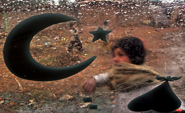 An Afghan refugee boy is seen through the windshield of a rickshaw during a rainy day in a poor neighborhood of Rawalpindi, Pakistan, Friday, Feb. 5, 2010. (AP Photo/Muhammed Muheisen)