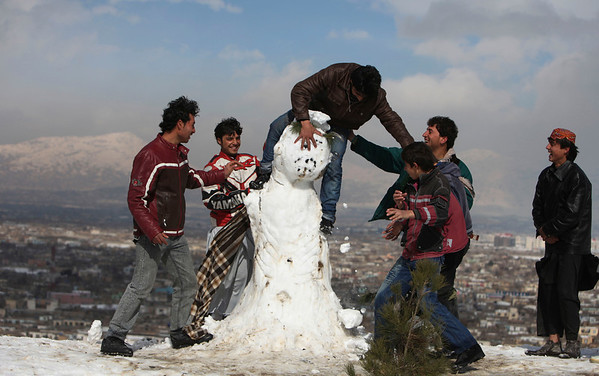 An Afghan man loses his balance as he tries to stand on top of a snowman in Kabul, Afghanistan, Monday, Feb. 8, 2010. (AP Photo/Altaf Qadri)