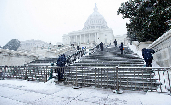 Employees of the Architect of the U.S. Capitol shovel the steps and treat it with ice melter, on Capitol Hill in Washington, Friday, Feb. 5, 2010, as snow began to fall in Washington area. (AP Photo/Manuel Balce Ceneta)