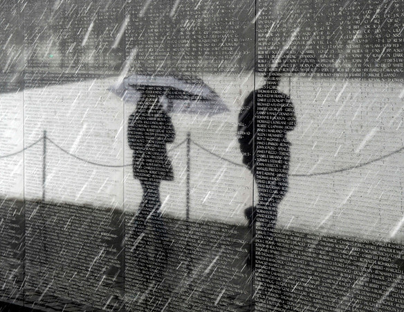 "People walk in the snow past the Vietnam War Memorial  in Washington, Friday, Feb.  5, 2010. The region's second snow storm in less than two months could be ""extremely dangerous,"" and heavy, wet snow and strong winds threatened to knock out power, the National Weather Service said. (AP Photo/Susan Walsh)"