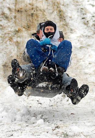 Daniel Watkins, Caroline Haynes and Jason Ruth fly over a bump as they sled at Craighead Forest Park in Jonesboro, Ark., Monday, Feb. 8, 2010. (AP Photo/The Jonesboro Sun, James Byard)