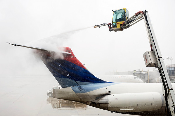 "A Delta airplane is de-iced at Washington's Ronald Reagan National Airport, Friday,  Feb. 5, 2010. The region's second snow storm in less than two months could be ""extremely dangerous,"" and heavy, wet snow and strong winds threatened to knock out power, the National Weather Service said.  (AP Photo/Cliff Owen)"