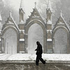A pedestrian walks past the entrance to Crown Hill Cemetery as snow falls in Indianapolis, Friday, Feb. 5, 2010.  A winter storm warning is in effect in Central Indiana until Saturday morning.  (AP Photo/Michael Conroy)