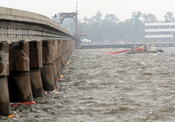 Workers spread oil booms along a railroad trestle that crosses the bay in Bay St. Louis, Miss., as preparations continue to head off damage from an inpending oil spill along the Gulf coast Friday, April 30, 2010.  (AP Photo/Dave Martin)