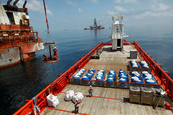 A worker is carried in a personnel basket from the Q4000 to the Joe Griffin in preparation to lower the containment vessel, seen on deck in background, over the oil leak at the site of the Deepwater Horizon rig collapse, Thursday, May 6, 2010.  (AP Photo/Gerald Herbert)