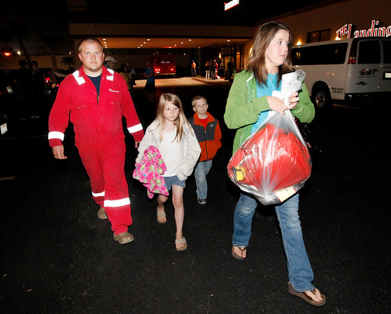 A crew member of the oil rig Deepwater Horizon, who identified himself only as Stenson, left, walks with his family to his car at a hotel in Kenner, La., after his crew boat returned to shore Thursday, April 22, 2010. Survivors of the thunderous blast aboard the oil platform off the Louisiana coast were being reunited with their families at a suburban New Orleans hotel early Thursday as the search for 11 missing workers continued. (AP Photo/Gerald Herbert)