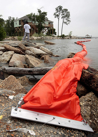 Leonard Lawton of Pass Christian, Miss., fishes next to an oil retaining boom in Bay St. Louis, Miss., Saturday, May 1, 2010. Environmentalists are concerned about the potential disaster the approaching oil slick presents.  (AP Photo/Dave Martin)