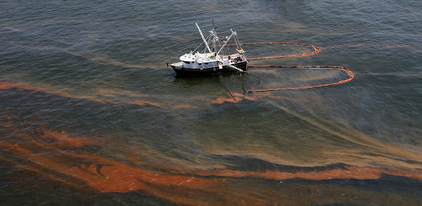 A shrimp boat is used to collect oil with booms in the waters of Chandeleur Sound, La., Wednesday, May 5, 2010.  (AP Photo/Eric Gay)