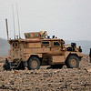 U.S. soldiers with NATO forces and Afghan security men are seen near a US military armored vehicle at the site of a suicide attack on a small group of tribal elders and government workers in Khogyani district near Jalalabad, Nangarhar province east of Kabul, Afghanistan, Monday, Feb. 22, 2010. Police say a suicide bomber has killed 15 people in eastern Afghanistan, including a key tribal leader who played a major role in the failed attempt to capture Osama bin Laden at Tora Bora in 2001. (AP Photo/Rahmat Gul)