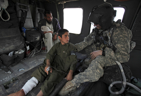U.S. Army flight medic Sgt. Nathaniel Dabney, of Prescott, Ariz., comforts an Afghan civilian boy with a gun shot wound just after take off on a U.S. Army Task Force Pegasus helicopter, with father of boy looking on from behind, during a medevac mission, in Helmand province, southern Afghanistan, Sunday Feb. 21, 2010.  Pegasus crews have come under fire nearly every mission while evacuating those wounded as U.S. and Afghan troops take part in the assault in the Taliban-held town of Marjah.  No names given and reason for gun shot wound unknown.(AP Photo/Brennan Linsley)