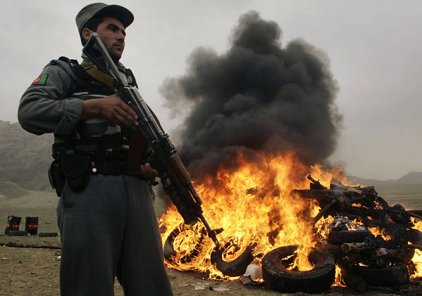 An Afghan policeman stands guard, as flames rise up during a drug burning ceremony in Herat, west of Kabul, Afghanistan on Sunday, Feb. 21, 2010. Around 1, 850 kilos of drugs were set on fire, as Afghanistan is the world's largest producer of opium, the raw ingredient for heroine, which is considered to be a major funding source for the Taliban. (AP Photo/Reza Shirmohammadi)