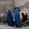 A young Afghan girl carries a child on her back as she walks behind two women at a market in Kabul, Afghanistan, Monday, Feb. 22, 2010.  (AP Photo/Altaf Qadri)