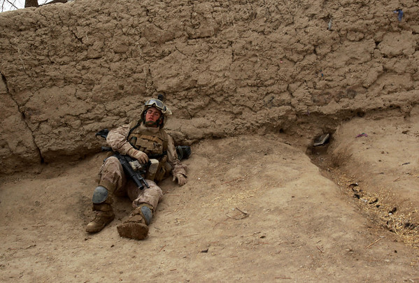 A U.S. Marine rests against a compound wall as they push on foot to the south of Marjah in Afghanistan's Helmand province on Sunday Feb. 21, 2010. (AP Photo/David Guttenfelder)