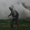 A U.S. Marine takes runs through a field after igniting a smoke grenade to mark a landing zone for a U.S. Army Task Force Pegasus helicopter during a medevac mission, in Marjah, Helmand province, Afghanistan, Sunday Feb. 21, 2010. Pegasus crews have come under fire nearly every mission in Marjah while evacuating the wounded, as U.S. and Afghan troops take part in an assault on the Taliban stronghold. (AP Photo/Brennan Linsley)