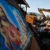 Images of Jesus Christ and the Virgin Mary sit on the rubble of a house as a machine clears debris in Iloca, Chile,  Wednesday, March 10, 2010.  An 8.8-magnitude earthquake hit central Chile last Feb. 27, causing widespread damage. (AP Photo/Fernando Vergara)