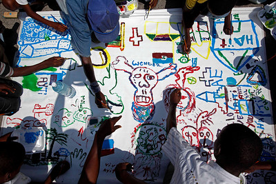 Children from a makeshift camp of earthquake survivors paint a mural as a group of Cuban artists organized activities to entertain them in Port-au-Prince, Wednesday, March 10, 2010. The 7.0-magnitude earthquake that hit Haiti on Jan. 12 left more than a million people living in makeshift camps. (AP Photo/Esteban Felix)