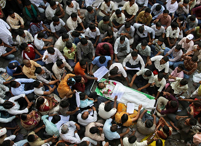 Students of Osmania University sit around the body of fellow student M Sai Kumar Yadav as they protest in Hyderabad, India, Tuesday, March 9, 2010. According to local news reports, Yadav hung himself to death demanding the creation of a separate Telangana state. In December, India's federal government had promised to carve out a new state called Telangana in the northern part of Andhra Pradesh state after a senior local politician went on a hunger strike to press the demand. But weeks later the government appeared to put the plan on hold and said more consultations were needed before the new state was formed. (AP Photo/Mahesh Kumar A)