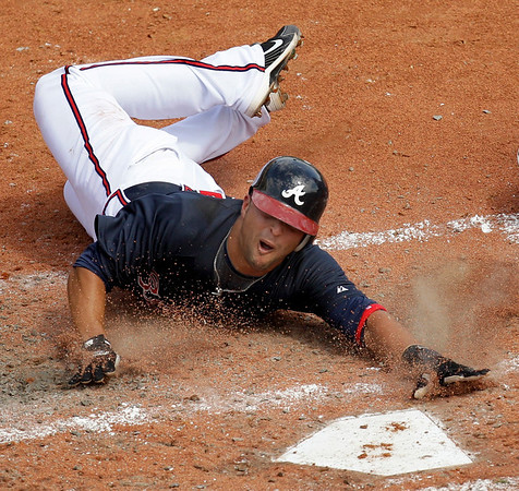 Atlanta Braves' Martin Prado scores on a single by Eric Hinske during the fourth inning of a spring training baseball game against the New York Mets on Wednesday, March 10, 2010 in Kissimmee, Fla. (AP Photo/Charlie Riedel)