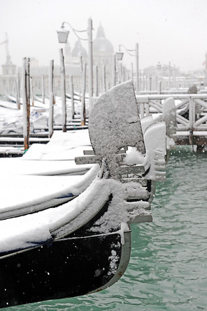Traditional Venetian gondolas are moored as a light snowfall has been blanketing the city of Venice, Italy, Wednesday, March 10, 2010. (AP Photo/Luigi Costantini)