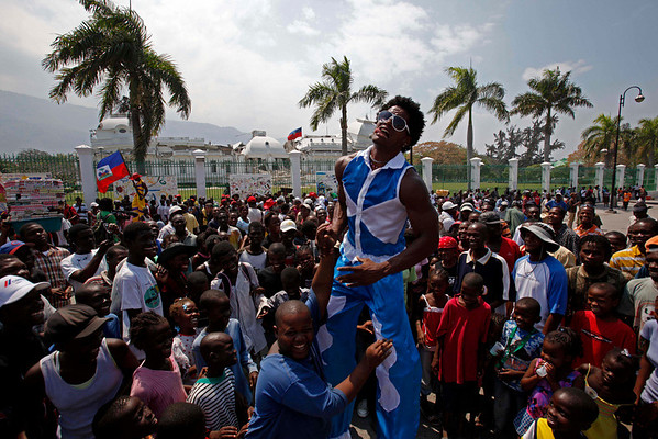 A Cuban artist on stilts gestures as he pretends to try to lift a youth as his group entertains earthquake survivors from the makeshift camp in front of the National Palace in Port-au-Prince, Wednesday, March 10, 2010. The 7.0-magnitude earthquake that hit Haiti on Jan. 12 left more than a million people living in makeshift camps. (AP Photo/Esteban Felix)
