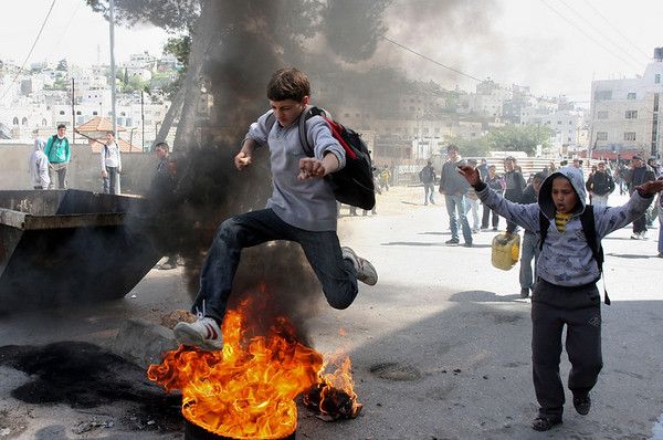 A Palestinian youth jumps over a burning tire during clashes with Israeli soldiers, not seen, in the West Bank city of Hebron, Wednesday, March 17, 2010. Israel on Wednesday lifted its tight restrictions on Palestinian access to Jerusalem's holiest shrine and called off an extended West Bank closure after days of clashes between Palestinians and Israeli security forces. While there were no reports of new clashes in Jerusalem, sporadic violence broke out Wednesday in the West Bank. (AP Photo/Nasser Shiyoukhi)