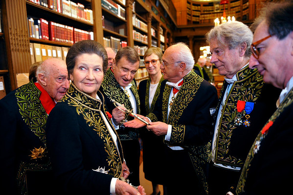 Simone Veil, dressed in the French Academician's uniform of a black jacket embroidered in green laurel leaves, speaks with Academicians in the library of the Institut de France before a ceremony in Paris Thursday, March 18, 2010. The name of Simone Veil, now 82, is synonymous with the battle that she spearheaded to legalize abortion in France. She has twice served as minister, for health and social affairs, and became the first woman president of the European Parliament. Veil, a French political icon who survived Nazi death camps and went on to become a moral figurehead for France, was inducted Thursday into the Academie Francaise, the sixth woman to cross the portals of the centuries-old institution. (AP Photo/Philippe Wopjazer, Pool)