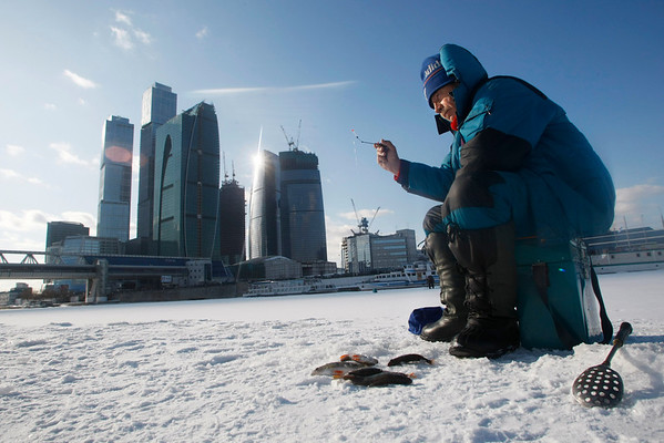 A man fishes on the Moscow River with city skyscrapers under construction in the background, in downtown Moscow, Wednesday, March 17, 2010. Temperature is still below zero, about -10 C (14 F). (AP Photo/Mikhail Metzel)