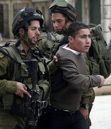 Israeli soldiers detain a Palestinian boy during clashes in the West Bank city of Hebron, Thursday, March, 18, 2010. Israel on Wednesday lifted its tight restrictions on Palestinian access to Jerusalem's holiest shrine and called off an extended West Bank closure after days of clashes between Palestinians and Israeli security forces. Sporadic violence broke out Thursday in the West Bank. (AP Photo)